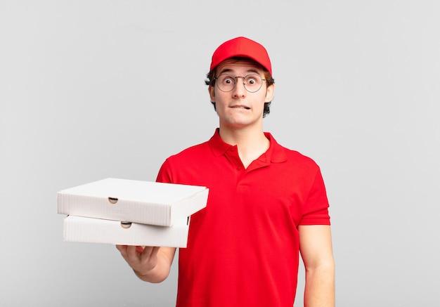 Pizzalieferjunge, der verwirrt und verwirrt aussieht, sich mit einer nervösen geste auf die lippe beißt und die antwort auf das problem nicht kennt