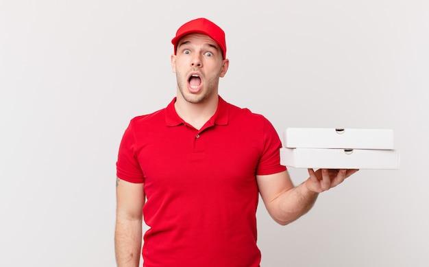 Pizzaliefermann sieht sehr schockiert oder überrascht aus und starrt mit offenem mund an und sagt wow