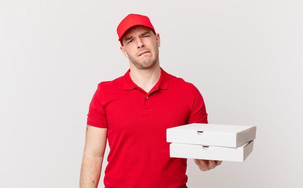Pizzaliefermann sieht verwirrt und verwirrt aus, beißt sich mit einer nervösen geste auf die lippe und kennt die antwort auf das problem nicht