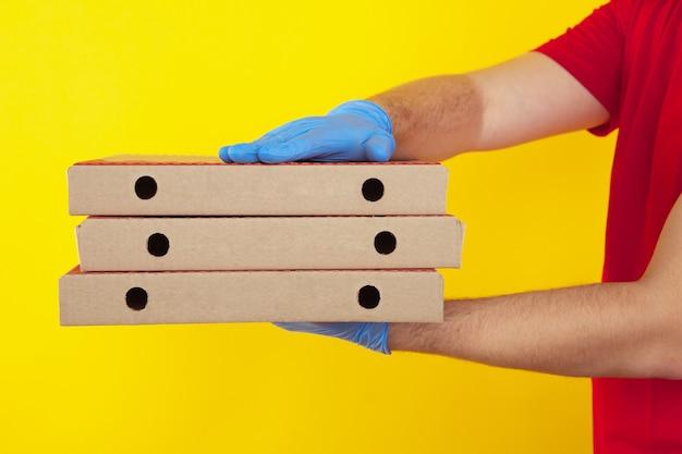 Pizzaschachteln zur lieferung. mann kurier in handschuhen.