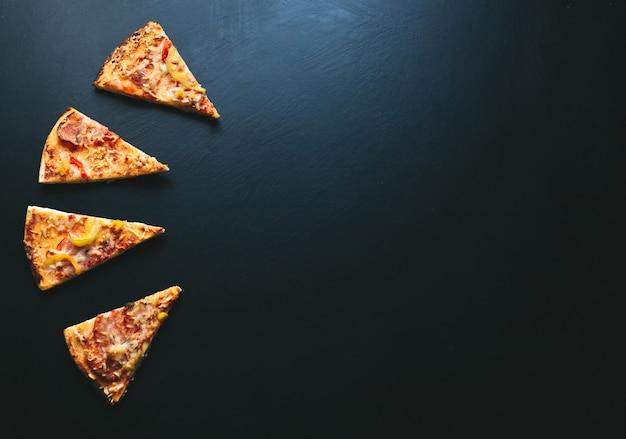 Pizzascheibe auf schwarzem hintergrund, mit platz für text. ansicht von oben