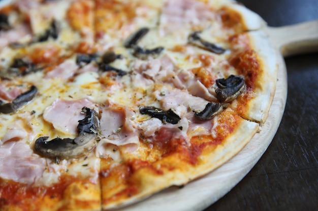 Pizzaschinken und -pilz auf holz