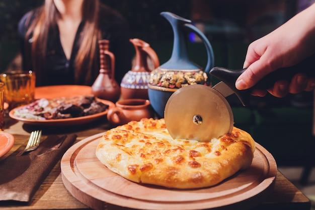 Pizzaschneider rad, das schinkenpizza mit paprika und oliven auf holzbrett auf tisch schneidet.