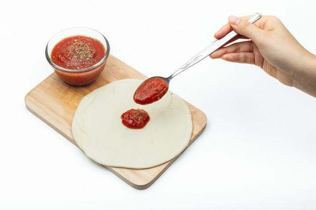 Pizzasoße auf pizzateig kleben