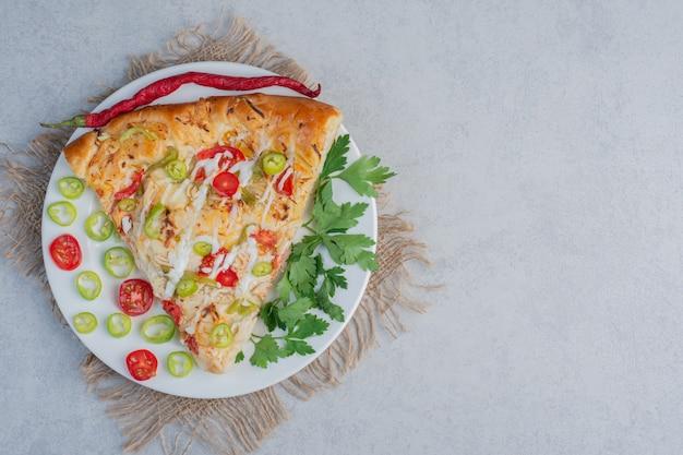 Pizzastück mit paprika und petersilienblättern auf marmoroberfläche