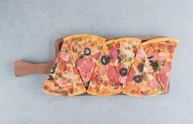Pizzastücke auf einem kleinen tablett auf marmor gebündelt