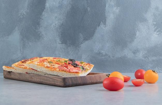 Pizzastücke auf einem tablett neben kleinen tomaten auf marmor