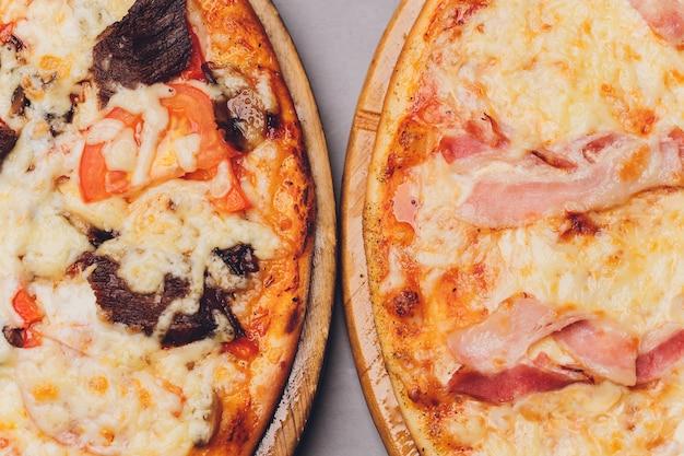 Pizzastücke auf rustikalem holztablett und dunklem hintergrund.