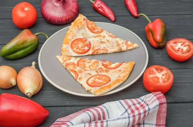 Pizzastücke mit käse und tomaten auf einem teller mit zutaten auf einem schwarzen hölzernen hintergrund.