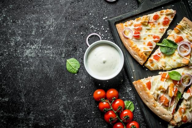 Pizzastücke mit tomaten und käsesauce in der schüssel. auf dunklem rustikalem hintergrund