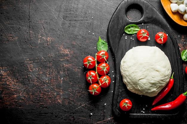 Pizzateig auf einem schneidebrett mit tomaten, mozzarella und spinat.