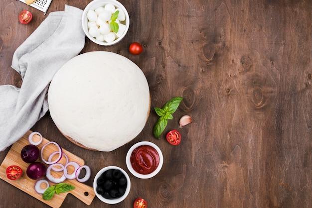 Pizzateig auf hölzernem hintergrund draufsicht