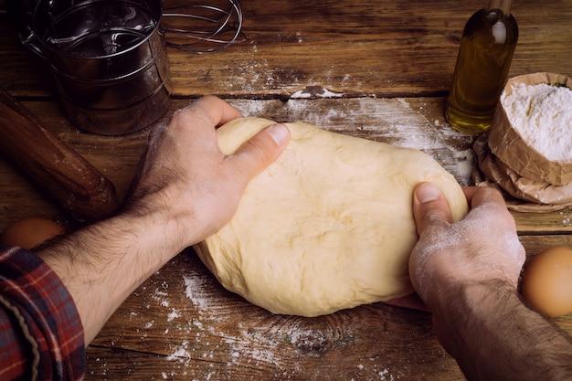 Pizzateig, der in der hauptküche kocht. hausgemachter teig für brot, pizza, gebäck und brötchen. teigbestandteile auf einem hölzernen rustikalen hintergrund