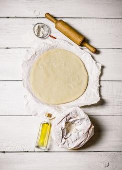 Pizzateig mit einem nudelholz auf einem weißen hölzernen hintergrund
