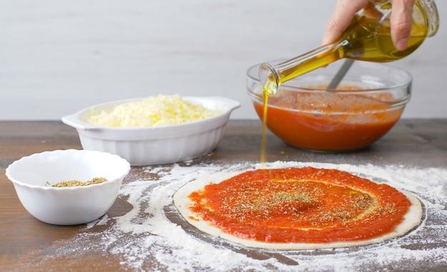 Pizzateig mit frischer tmatosauce und oregano. italienisches traditionelles rezept der pizza