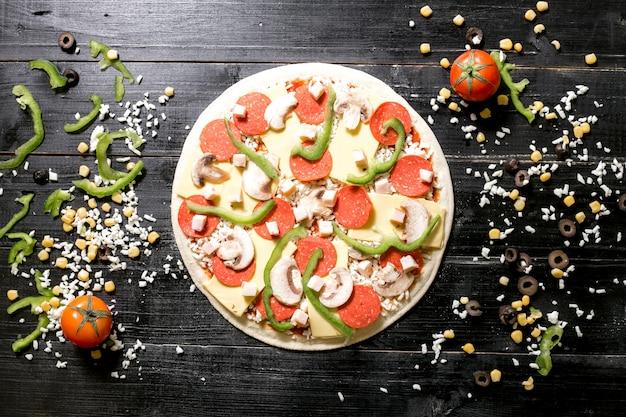 Pizzateig mit peperoni-pilz-käse oben neben käse streut olivenmaistomate