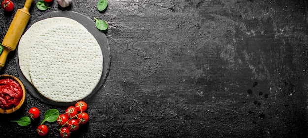Pizzateig mit tomatenmark, spinat und kirsche ausgerollt. auf schwarzem rustikalem hintergrund