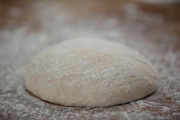 Pizzateig und mehl auf rollbrett