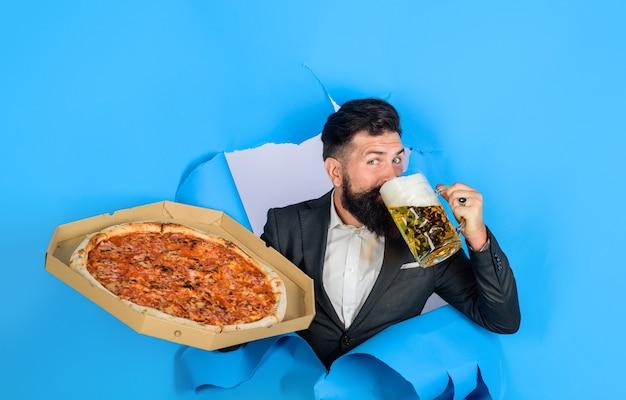 Pizzazeit bärtiger mann mit leckerer pizza und bier, der durch ein papierloch schaut, zufriedener mann mit bart