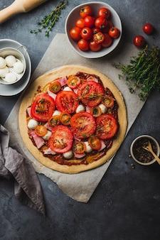 Pizzazubereitung. rohe pizza. vollkornteig auf backblechen mit verschiedenen zutaten zum kochen von pfeffer, mozzarella, tomate, tomatensauce, schinken, thymian und nudelholz ausrollen.