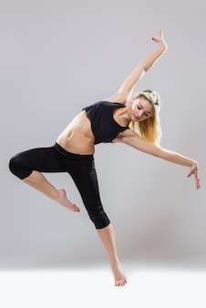 Pj-tanz, junger schöner tänzer, der auf einem studio lokalisiert auf weißem hintergrund aufwirft