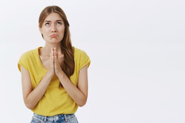 Plädierendes schmollendes mädchen, das um hilfe bittet, um entschuldigung bittet und traurig verzieht das gesicht