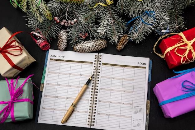 Pläne für das neue jahr. offenes tagebuch auf tisch mit geschenkboxen und tannenzweigen