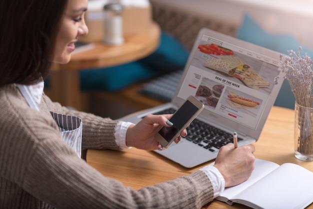 Pläne für den tag. angenehme lächelnde frau, die notizen macht und handy beim sitzen vor laptop verwendet.