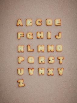 Plätzchen abc in form von alphabet az auf braunem papphintergrund