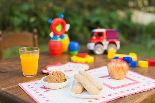 Plätzchen, apfel und glas saft auf einer tabelle im freien