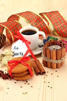 Plätzchen für den weihnachtsmann: konzeptbild von ingwerplätzchen, milch und weihnachtsdekoration auf hellem hintergrund