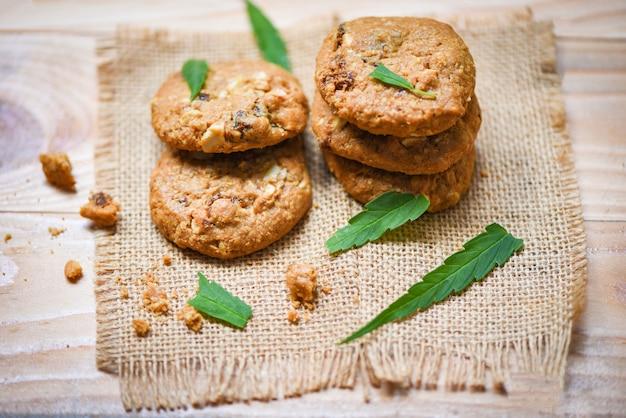 Plätzchen mit hanfblatt-marihuanakraut auf hölzernem hanflebensmittelsnack des sacks für gesundheit