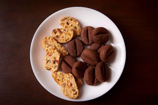 Plätzchen mit rosinen und nüssen auf einer weißen platte.