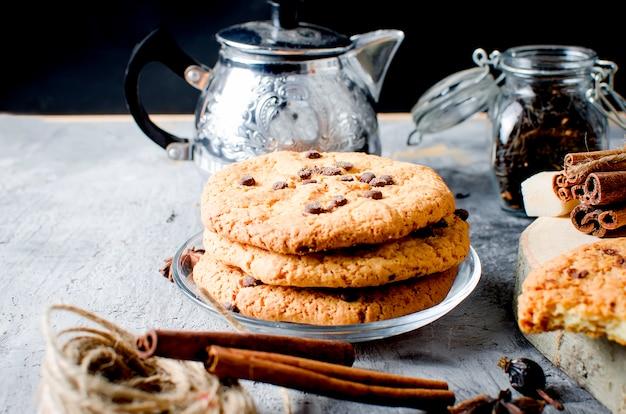 Plätzchen mit schokoladenplätzchen, tasse tee, zimt, anis auf dunklem hintergrund