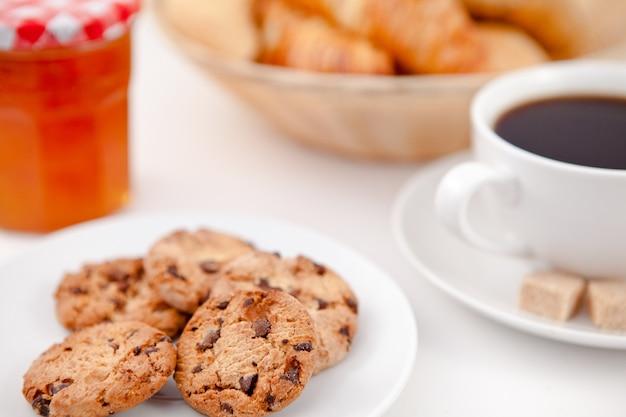 Plätzchen und eine tasse kaffee auf weißen platten mit zuckerhörnchen und milch und ein topf marmelade