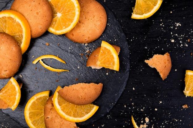 Plätzchen und orange zitrusfrucht auf schieferplatte auf schwarzem. flach liegen