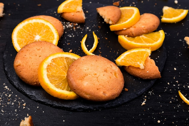 Plätzchen und orange zitrusfrucht auf schieferplatte auf schwarzem.