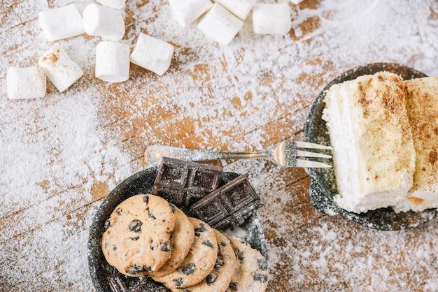 Plätzchen und schokolade mit kuchen auf verzierter tabelle