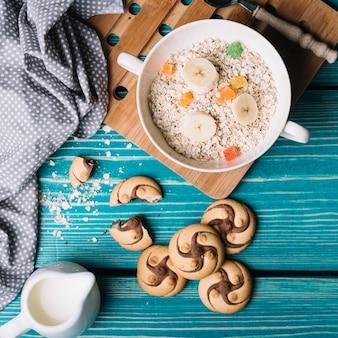 Plätzchen und trockene hafer mit bananenscheibe und geleesüßigkeiten in der schüssel