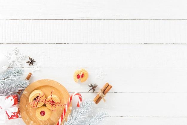 Plätzchen, zuckerstange und weihnachten, die einzelteile auf weißem hölzernem bretthintergrund mit schnee verzieren