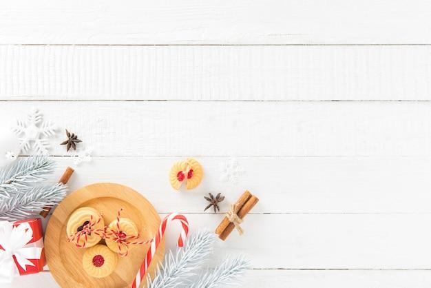 Plätzchen, zuckerstange und weihnachten, die einzelteile auf weißem hölzernem bretthintergrund verzieren