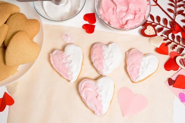 Plätzchenherz verziert mit glasurweiß und rosa für valentinstag, nahaufnahme, backen für den feiertag. dekorative herzen draufsicht.