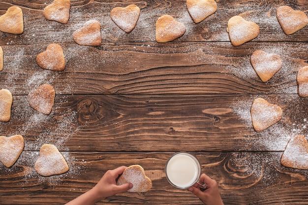 Plätzchenherzform besprüht mit puderzucker auf einem hölzernen hintergrund. in den händen von keksen und becher mit milch. kopieren sie platz