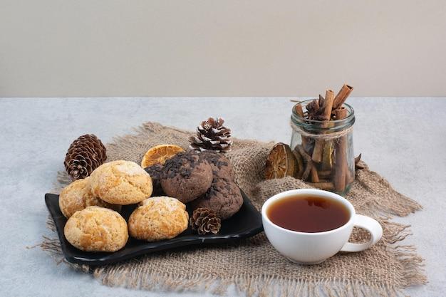 Plätzchenteller, tee, zimt und pinecones auf leinwand. foto in hoher qualität