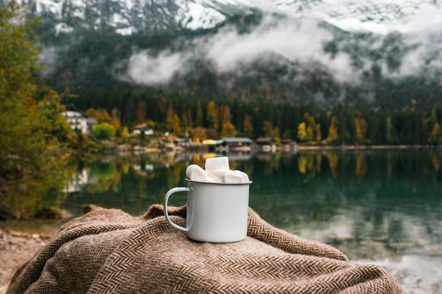 Plaid, kakao mit marshmallow nahe see in den bayerischen alpen, deutschland