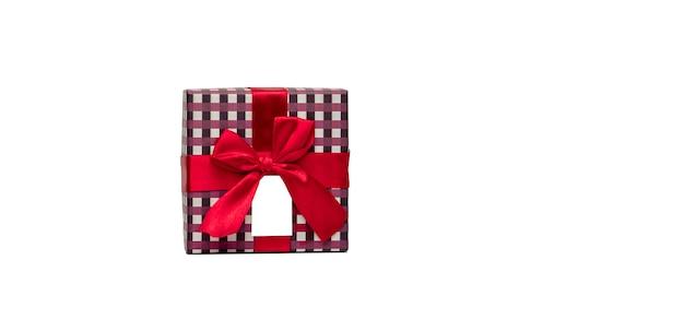 Plaidmuster-geschenkbox mit rotem bandbogen und der leeren grußkarte, die auf weißem hintergrund mit kopienraum lokalisiert wird, addieren einfach ihren eigenen text. verwenden sie für weihnachten und neujahr