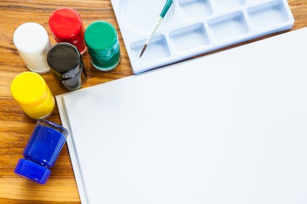 Plakat-farbenflasche, bürste, palette, zeichnungsbuch mit kunst für kind und kopienraum auf holz