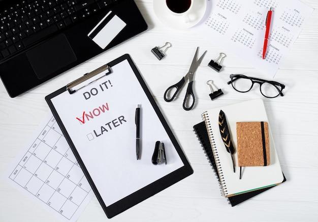 Plakat mit motivationswörtern zur arbeit an der draufsicht des bürogeschäftsschreibtisches