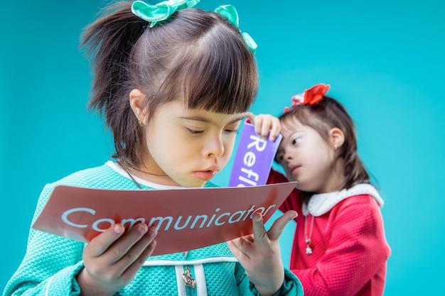 Plakate in händen. dunkelhaarige mädchen mit down-syndrom sehen beim lesen von postern in farbigen kleidern hübsch aus