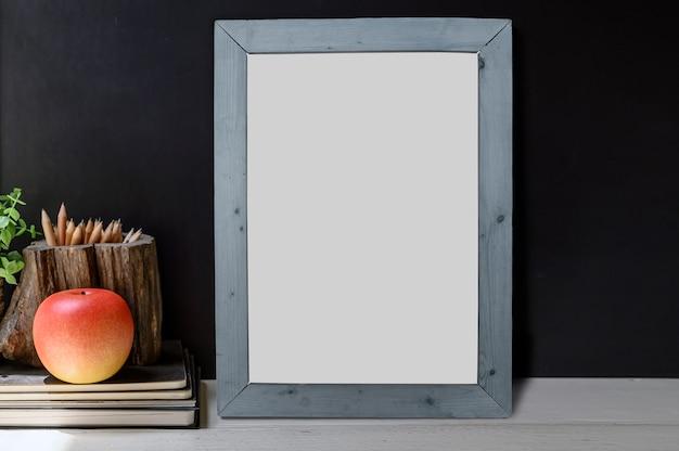 Plakatmodell mit apfel auf dem buch auf holztischschwarzfarbwandhintergrund